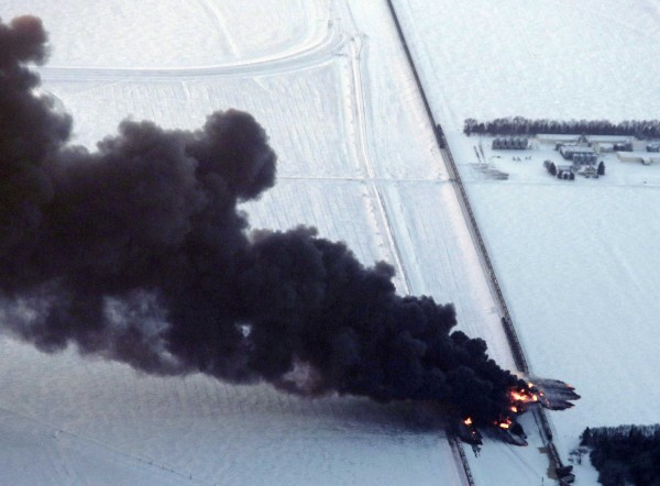 Smoke rises from scene of a derailed train near Casselton, North Dakota December 30, 2013. A BNSF train carrying crude oil in North Dakota collided with another train on Monday, setting off a series of explosions that left at least 10 cars ablaze, the latest in a string of incidents that have raised alarms over growing oil-by-rail traffic.