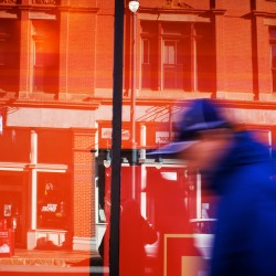 A man turns into a streak of blue bustling by an orange window at the Maine College of Art on Congress Street.