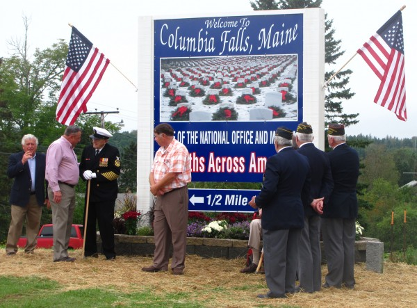 Gov. Paul LePage (second from left) talks with retired U.S. Navy Chief Petty Officer Robert Coles during a ceremony to unveil a new sign directing drivers on U.S. Route 1 in Columbia Falls to a new museum for the Wreaths Across America program.