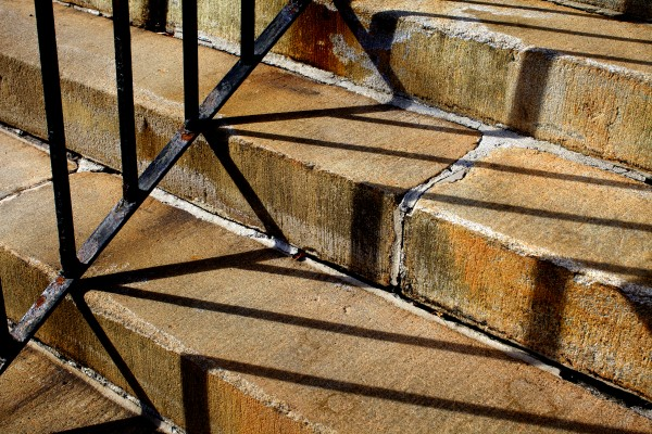 Stone steps, a handrail and the afternoon sun tangle in shadows in Portland.