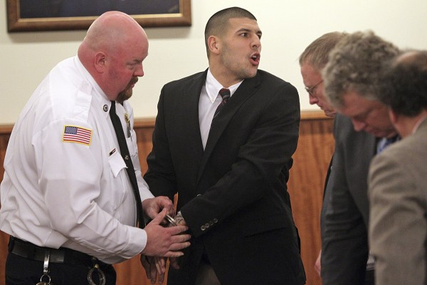 Former New England Patriots player Aaron Hernandez mouths words with family members after he appeared in court at the Fall River Justice Center in Fall River, Massachusetts December 23,  2013. The former NFL tight end is charged in the fatal shooting of his friend, Odin Lloyd, in June 2013.