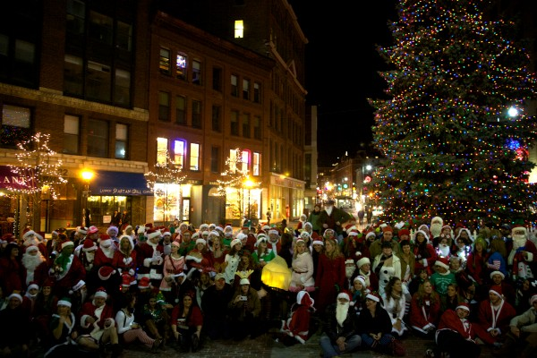 Several hundred Christmas-costumed bar crawlers pose for a group photo in Portland's Monument Square Saturday night during this year's Santacon event.