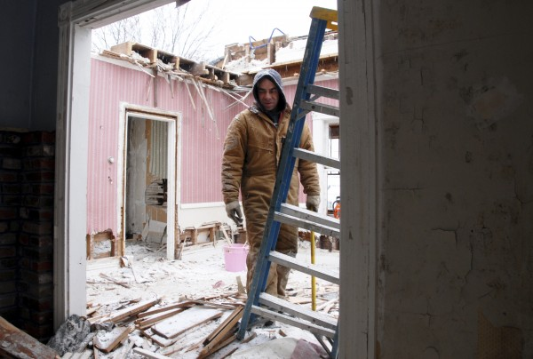 Millinocket contractor Grant Boynton reaches for a ladder while working on the demolition of a Lincoln Street house in Millinocket on Thursday, Jan. 27, 2011.