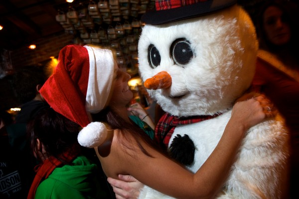 Colleen Young gets friendly with Jason Marineau who wears a snowman suit for Santacon in Portland's Old Port Saturday night.
