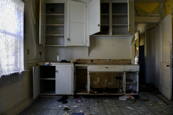 This photo shows the kitchen area of an abandoned Aeon Group property in Cleveland. Aeon foreclosed on dozens of houses and abandoned them when they did not sell, leaving rotting porches, shattered windows and collapsed walls,