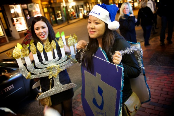 Dressed as a menorah and a dreidle, Rachel Yalowich (left) and Belle Bocal bring a a little diversity to Santacon in Portland Saturday night.