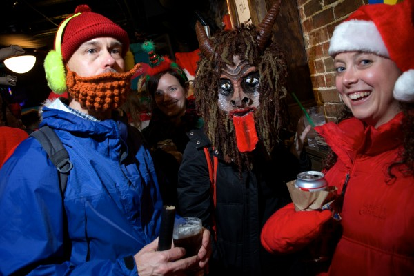 Bryan Connelly, dressed as Yukon Cornelius, AdriAnne Curtis, wearing a Krampus mask and Katy Nicketakis, wearing a Santa hat, enjoy Santacon at the Oasis in Portland Saturday night. Krampus is a character from Germanic folklore who punishes bad children at Christmastime.