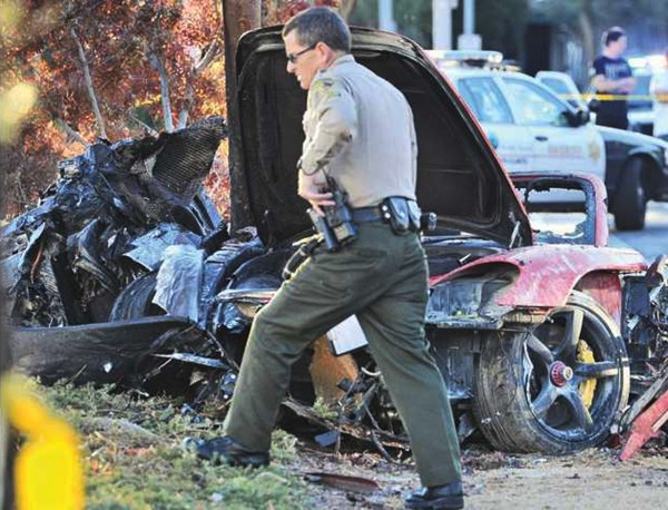 A police officer walks past the car where actor Paul Walker was killed along with another unidentified man during a car crash in Valencia, Santa Clarita, California, November 30, 2013. Walker, 40, who was in five of the six &quotFast and the Furious&quot action movies about illegal street racing and heists, was a passenger in a friend's car and was attending a charity event, according to a message linked to his Twitter account.