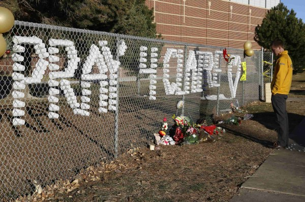 An Arapahoe high school student prays at the school in Centennial, Colorado December 15, 2013. Claire Davis, a 17-year-old Colorado high school senior shot in the head December 13 by a heavily-armed classmate who stormed the school remained in critical condition, the county sheriff said.