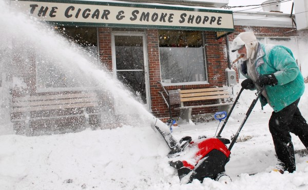 Frank Coglitore starts clearing snow Sunday morning in front of Cigar Shop on Main Street in Bangor.