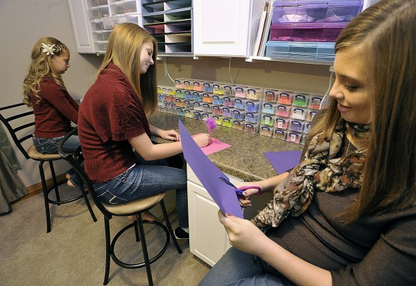 Kelsey Hooten, 16, right, works on an art project with sisters Hannah, 11, left, and Lexie, 14, at home in Dayton, Ohio, on Nov. 15, 2014. Because of bullying at school, Kelsey enrolled in a K-12 online school and all three sisters attend the online school at differing grade levels.