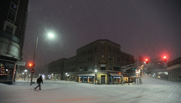 A pedestrian walks on the deserted streets of downtown Bangor in pre-dawn darkness on Sunday.
