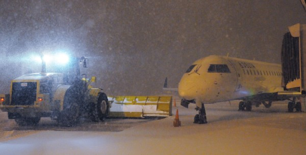 Snow removal equipment pushes snow away from a plane that is scheduled to depart BIA this morning. Most incoming flights are cancelled due to snow conditions.