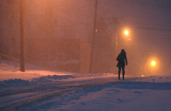 A woman runs up Union Street in Bangor in the pre-dawn darkness of Sunday's snow storm.