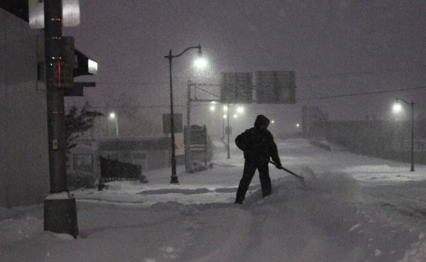 A man shovels snow from the sidewalk on Union Street in Bangor in the pre-dawn darkness of Sunday's snow storm.