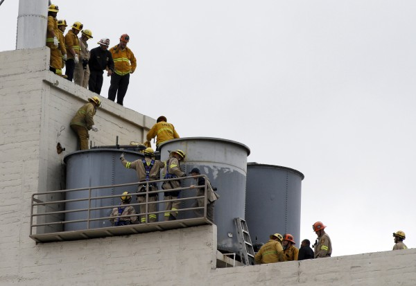 Firefighters work to remove a body found inside a water tank on the roof of Hotel Cecil in Los Angeles, Calif., on Feb. 19, 2013. Police determined the body was that of a 21-year-old Canadian woman who went missing while staying there more than two weeks ago. Elisa Lam, a student from Vancouver, British Columbia, who was visiting Southern California on her own, was last seen at the Cecil Hotel in downtown Los Angeles on Jan. 31 and authorities had characterized her disappearance as suspicious.