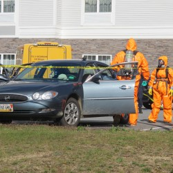 In this October 2013 file photo, police in safety suits examine a car in an Ellsworth hotel parking lot as part of a mobile meth lab investigation. Three people from Aroostook County have been arrested in connection with the bust, which police say included the production of methamphetamine in a pickup truck in the same parking lot.