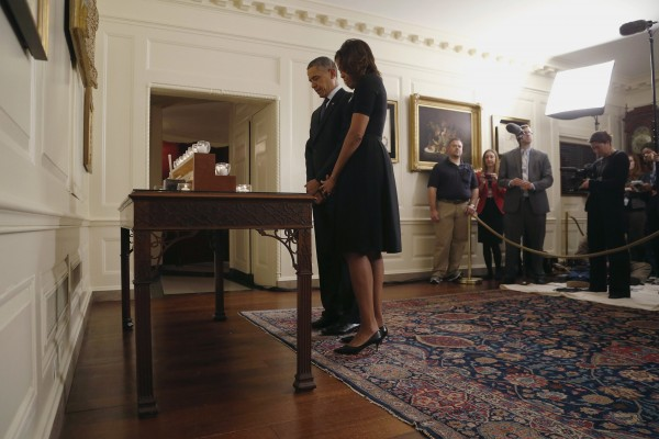 President Barack Obama and first lady Michelle Obama observe a moment of silence after lighting candles in memory of the 20 children and six school workers killed by a gunman at Sandy Hook Elementary School one year ago, in the Map Room at the White House in Washington, Dec.14, 2013.