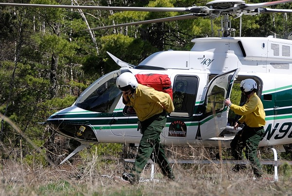 Forest rangers deploy from a Maine Forest Service Bell 407 helicopter after landing near a simulation burn site for their media demonstration in Township 32 MD Monday morning, May 2, 2011.