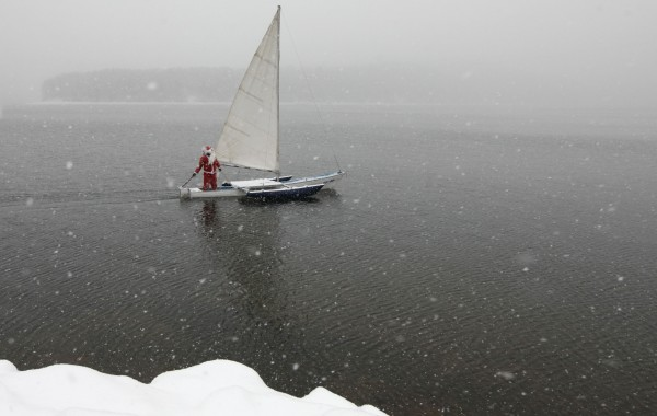 A member of the &quotSkipper&quot yacht club dressed as Santa Claus, sails his trimaran to mark the ending of the sailboat season during heavy snowfall at an air temperature of above minus 8 degrees Celsius (17.6 Fahrenheit) on the Yenisei River, outside Russia's Siberian city of Krasnoyarsk, December 18, 2013.