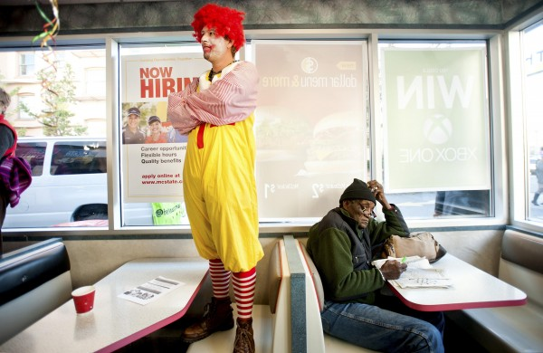 A McDonald's patron reads a newspaper while a demonstrator dressed as Ronald McDonald protests for higher wages in Oakland, California on Dec. 5. About 200 protesters filled the restaurant as several smiling employees filmed with their cell phones. Fast-food workers conducted a daylong nationwide strike demanding a $15 dollar minimum wage.