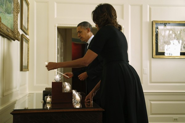 President Obama and first lady Michelle light candles in memory of the 20 children and six school workers killed by a gunman at Sandy Hook Elementary School one year ago, in the Map Room at the White House.