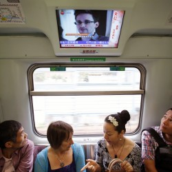 Passengers watch a television screen broadcasting news on Edward Snowden, a contractor at the National Security Agency (NSA) of the U.S., on a train in Hong Kong June 14, 2013.