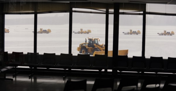 Snow removal equipment clears snow from the tarmac at Bangor International Airport on Sunday morning. While some flights into Bangor are canceled at their origin, Allegiant has two planes in the air headed to Bangor from Florida to take passengers to a warmer climate, according to assistant airport manager James Cander.