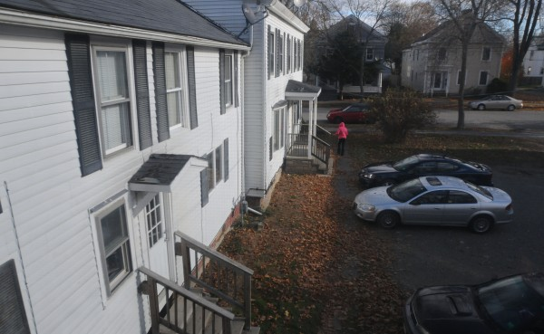 A neighbor walks out of her apartment at 166A Essex Street in Bangor to get her mail the morning after her neighbor Zackery Mailloux was arrested and charged with killing a woman at his apartment. Mailloux's blue sedan still sits in the driveway.