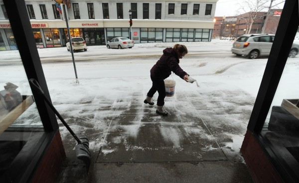 Hanna Bonaiuto spreads salt on the sidewalk in front of Verve Burritos in downtown Bangor on Sunday morning.