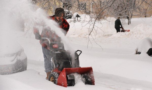 Chris Seekings clears snow from the driveway of his Brewer home Monday morning.