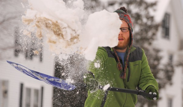 Sherman Bronson shovels the snow from the driveway of his Brewer home Monday morning. The overnight storm dumped about a foot of snow on the region.