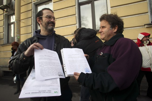 Greenpeace activist Dimitri Litvinov (left) and Peter Willcox, captain of the Greenpeace ship Arctic Sunrise, show papers certifying the termination of prosecution after they walked out of the offices of the Federal Migration Service Department in St. Petersburg, on Dec. 25. Russia on Wednesday formally dropped criminal charges against Greenpeace activists arrested in a protest against Arctic oil drilling and was expected to shortly do the same for all 30, the environmental group said. Willcox has returned to the U.S. after two months imprisonment in Russia, according to the Greenpeace USA Facebook page.