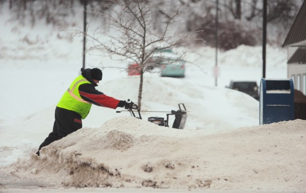 A man blows snow along Main Street in Bangor on Sunday morning.