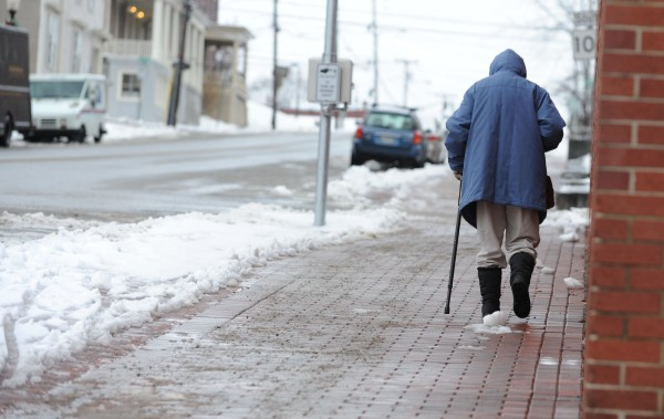 An elderly lady makes her way up a slick sidewalk along Hammond Street in Bangor on Monday after several inches of wet snow fell overnight.