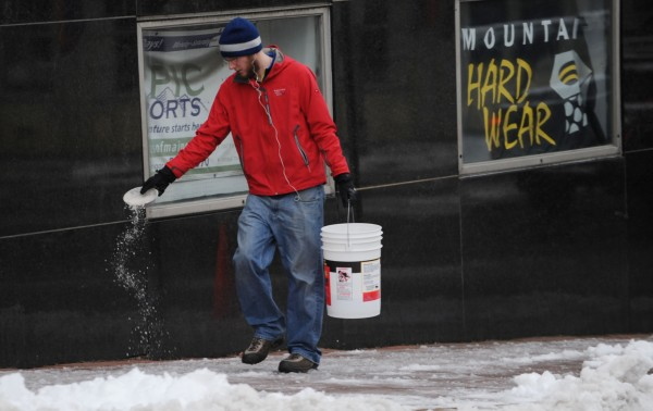 Salt is spread on a sidewalk on Hammond Street after Monday's storm dropped wet snow on the region.