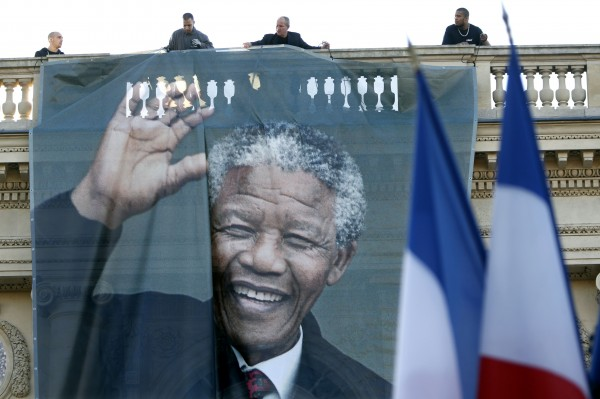 Workmen unfurl a giant banner with a photo of the late South African President Nelson Mandela to cover the facade of the Quai d'Orsay Foreign Affairs Ministry in Paris, December 6, 2013.
