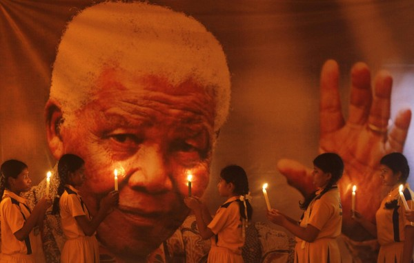 Schoolgirls hold candles in front of a poster of former South African President Nelson Mandela during a prayer ceremony at a school in the southern Indian city of Chennai December 6, 2013.