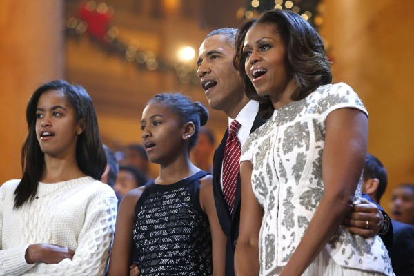 President Barack Obama and first lady Michelle Obama sing Christmas carols with daughters Malia (left) and Sasha during a taping of the Christmas in Washington television benefit program at the National Building Museum in Washington on Dec. 15, 2013.