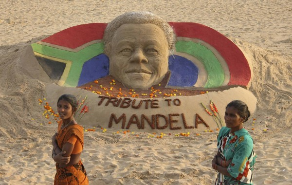 Women walk past a sand sculpture paying tribute to former South African President Nelson Mandela created by Indian sand artist Sudarshan Pattnaik, at Puri in the eastern Indian state of Odisha December 6, 2013.