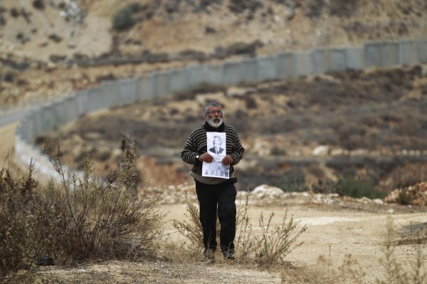The controversial Israeli barrier is seen in the background as a Palestinian protester walks with placards depicting former South African President Nelson Mandela during a weekly demonstration against Jewish settlements in the West Bank village of Bilin, near Ramallah December 6, 2013.