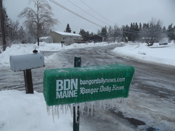 Icicles dangle from a Bangor Daily News box and a mailbox on a slushy, ice-covered street in a Machias neighborhood Sunday morning.