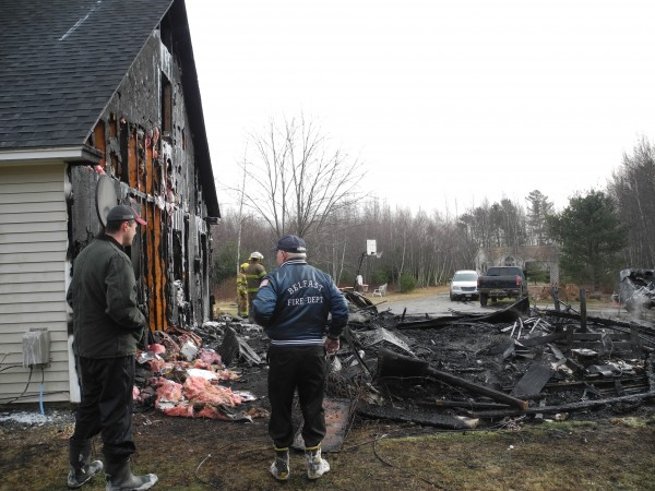 Homeowner Josh Brown, left, confers with Belfast Fire Chief Jim Richards Sunday as firefighters from three communities finished extinguishing the fire that consumed part of his Blueberry Lane home.