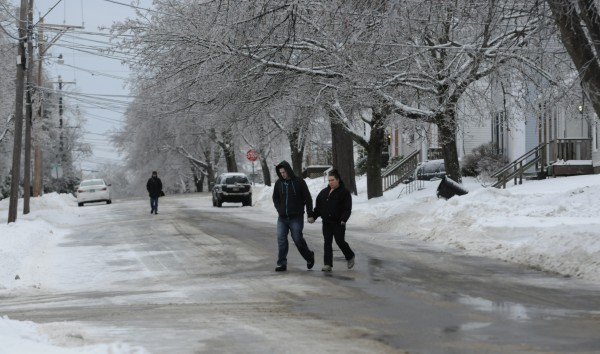 Ice-laden trees hang over the snow-covered streets of Bangor as pedestrians venture out on Tuesday morning.