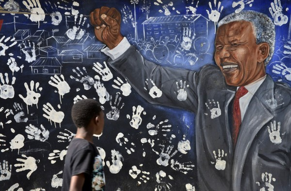 A boy walks past a mural painted outside the house former South African President Nelson Mandela once lived in, in Johannesburg's Alexandra township June 9, 2013.