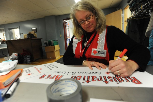 Red Cross shelter manager Joanne Harriman makes a sign on Tuesday at the Brewer Auditorium as she and other members of the Red Cross prepare to offer food and a cot to those who are without power and in need of shelter during the ice storm.