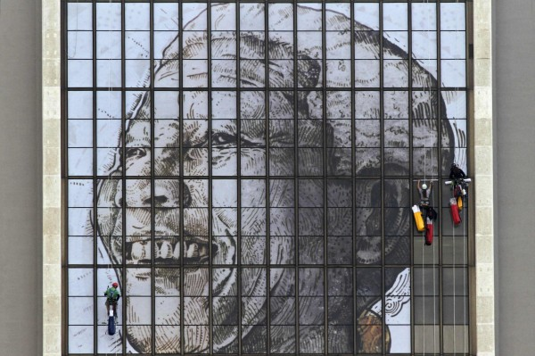 Rope access technicians work to complete a huge portrait of former South African President Nelson Mandela on the windows of the Civic Centre building in Cape Town, June 15, 2013.