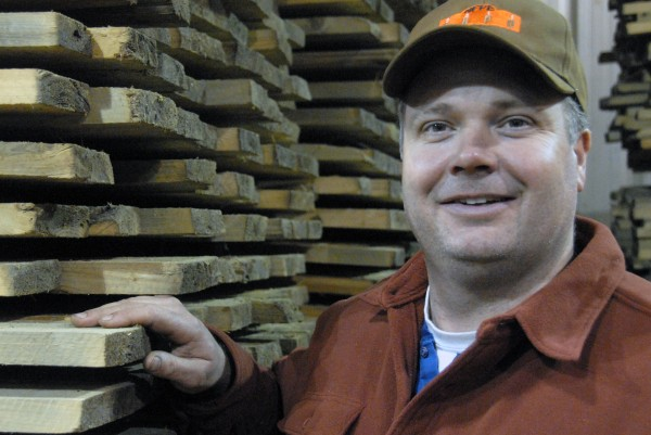 Steve Sanders, co-owner of West Branch Heritage Timber LLC., stands by finished flooring at his mill off Golden Road in 2011.