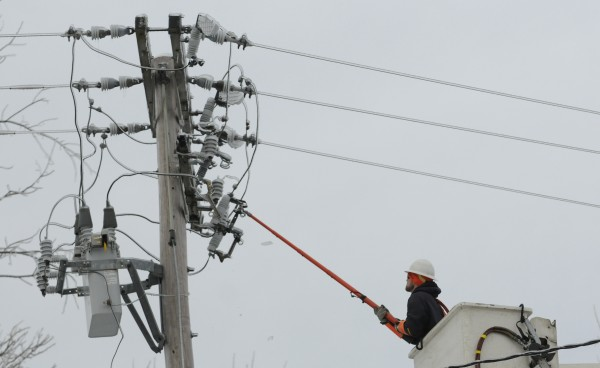A crew member with On Target Utility Services of Gardiner works on a power line along Route 46 in Eddington on Tuesday. On Target Utility Services is assisting Bangor Hydro in restoring power to communities in areas hit hard by the ice storm.