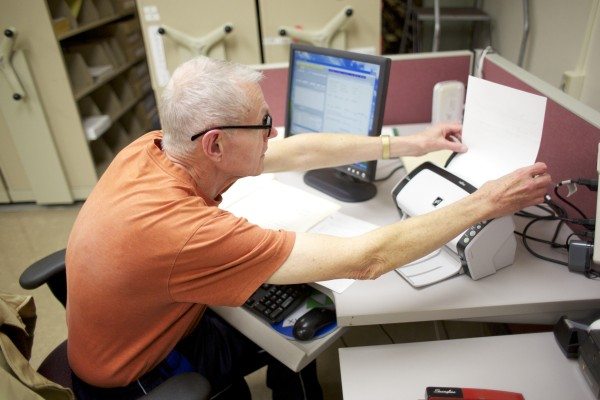 Volunteer John Doran of the Penobscot County Probate Court scans in documents from 2003 to add to the electronic record system Oct. 30 at the Penobscot County court building in Bangor.
